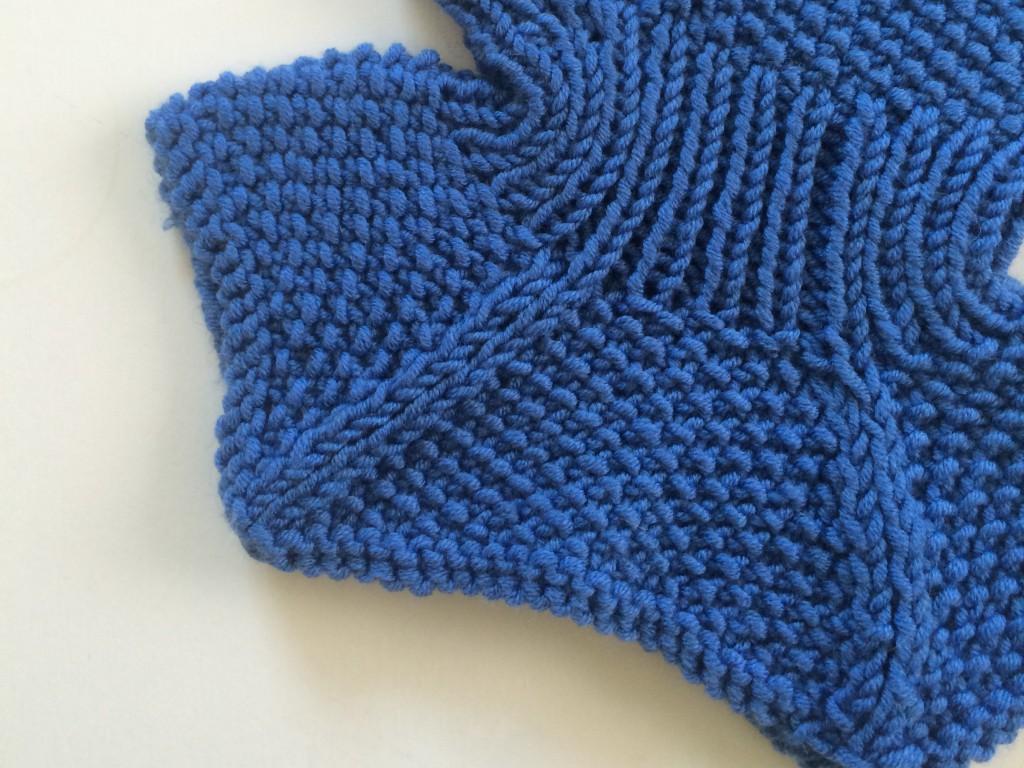 Detaljer fra en lue som er strikket i perlestrikk.