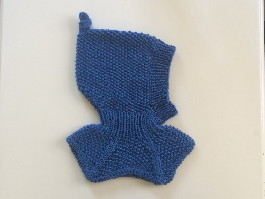 Råtasslue strikket i ett stykke med raglandsfelling i halsen.